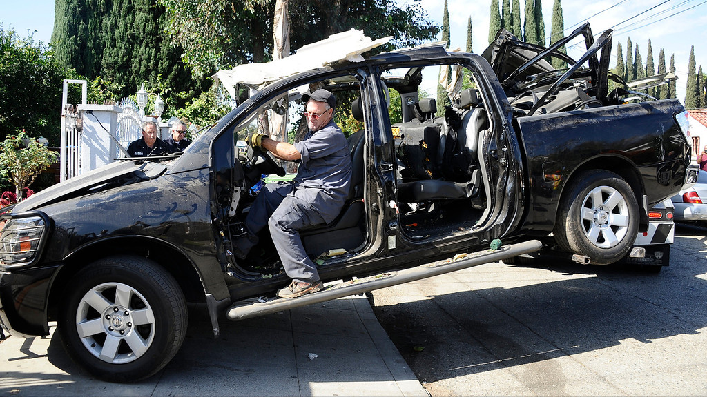 . Tow truck driver guides out of whats left of a nissan pickup truck that had  propane tanks inside exploded and rocked a North Hollywood neighborhood early Tuesday.  The blast happened in the 11000 block of Miranda Street around 12:30 a.m. Several 911 calls were received about some sort of explosion. Officials have determined the explosion happened inside the pickup truck.  When first responders arrived at the scene, they found the truck parked in a rear yard. When they got closer, they saw at least one propane tank inside the vehicle and backed off. North Hollywood CA. Oct 22,2013.  Photos by Gene Blevins/LA Daily News