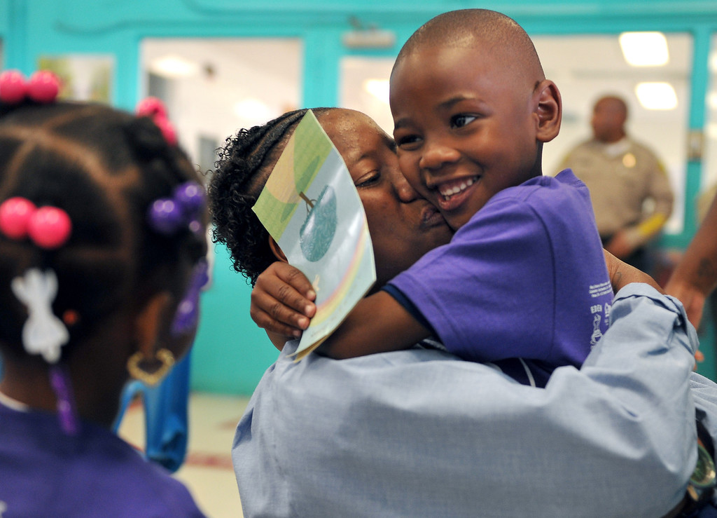 . 5/4/13 - Leneice Pattan, of Los Angeles, hugs her son Jacari Walker, 5,  during a visit at the California Institution for Women. The mothers and children were united by the non-profit organization entitled Get On The Bus which provides an annual event of free transportation for the children and their caregivers to the prison. The visit becomes more of an event, with snacks, lunch, arts, crafts, photos, keepsakes and plenty of hugs and kisses. The program began in 2000 with one bus one prison and 17 kids. Today children are able to visit their mothers and fathers with 60 buses, seven prisons and more than a thousand kids. Photo by Brittany Murray / Staff Photographer