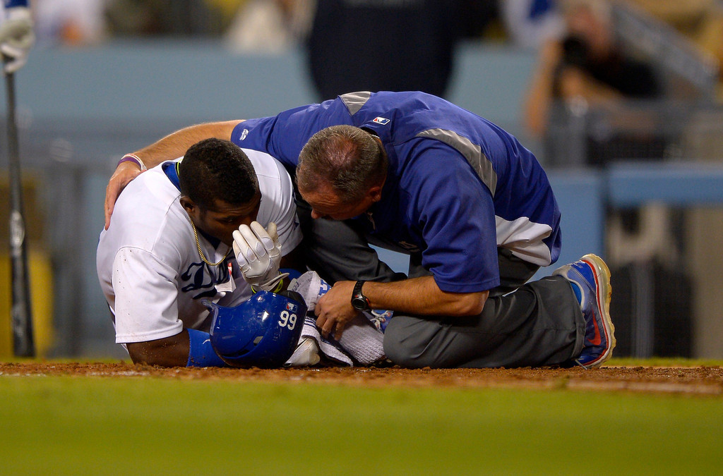 . Los Angeles Dodgers\' Yasiel Puig, left, is seen to by a trainer after being grazed by a pitch during the sixth inning of their baseball game against the Arizona Diamondbacks, Tuesday, June 11, 2013, in Los Angeles.  (AP Photo/Mark J. Terrill)