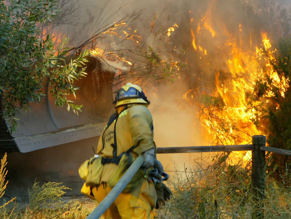 . 10-24-03...Val Verde Park fire...Photo of LA county firefighter as he gets help from dozer 7 stop the spreading  on a 200+acre brush fire that is still burning, more info from fire dept.Photo by Gene Blevins/LA Daily news
