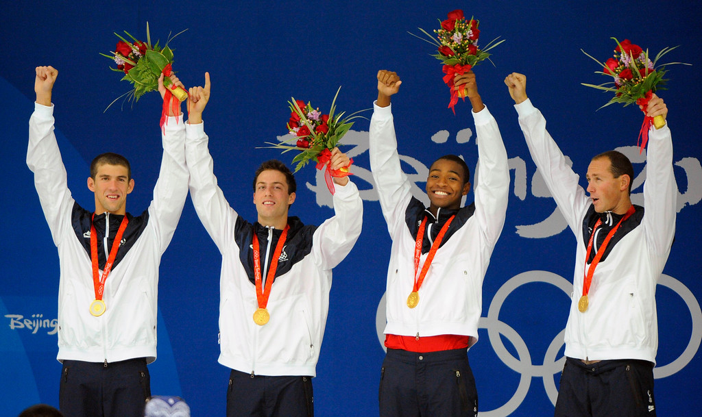 . Members of the U.S. relay team wave  with gold medals during an awarding ceremony after setting a world record in the men\'s 4x100-meter freestyle relay final at the Beijing 2008 Olympics in Beijing, Monday, Aug. 11, 2008. They are from left: Michael Phelps, Garrett Weber-Gale, Cullen Jones and Jason Lezak. (AP Photo/Mark J. Terrill)