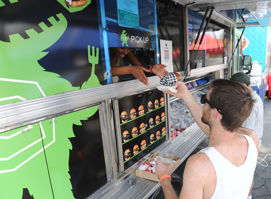 ". (John Valenzuela/Staff Photographer) Austin Johnson of Moreno Valley grabs his sliders from the ""Me So Hungry food truck during the second annual Food Truck and Brewfest in Redlands Saturday, June 29, 2013."