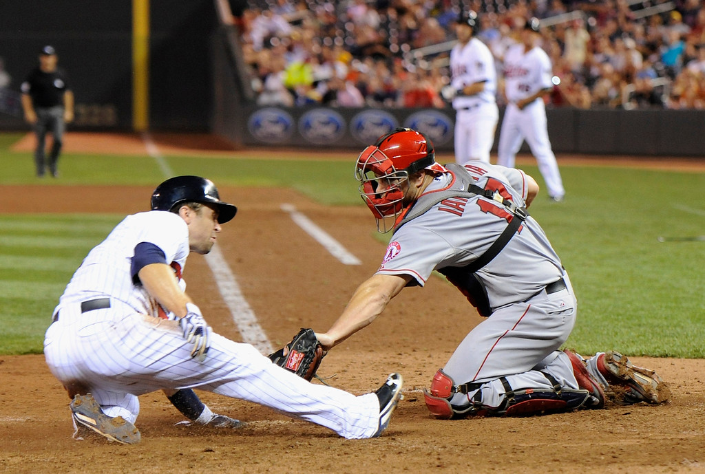 . MINNEAPOLIS, MN - SEPTEMBER 9: Brian Dozier #2 of the Minnesota Twins slides safely as Chris Iannetta #17 of the Los Angeles Angels of Anaheim defends home plate during the seventh inning of the game on September 9, 2013 at Target Field in Minneapolis, Minnesota. (Photo by Hannah Foslien/Getty Images)