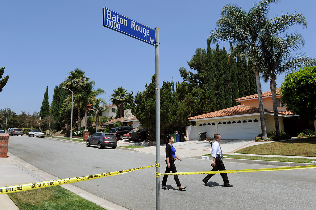 . LAPD detectives walk the scene on the 19200 block of Kenya Street in Northridge, Friday, June 15, 2013, where a woman was murdered and the suspect surrendered to SWAT officers following a nighttime standoff. (Michael Owen Baker/Staff Photographer)