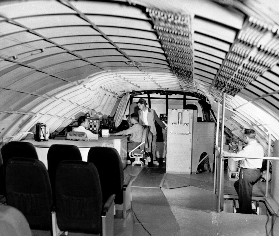. Millionaire aviator and industrialist Howard Hughes looks over the multi-metered engineer\'s panel of his huge flying boat at Los Angeles Harbor, Oct. 31, 1947.  Engineer Chal Bowen sits in front of the panel.  The eight-engine aircraft, weighing more than 200 tons, is expected to taxi 80 miles per hour.  (AP Photo)