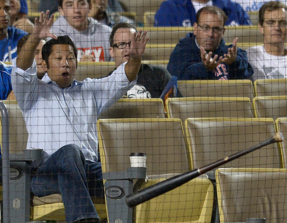 . A fan reacts to a bat that hit the screen in front of him that was lost after a swing by Willin Rosario in the 9th inning. The Dodgers defeated the Colorado Rockies at 4-2 Dodger Stadium in Los Angeles, CA. 6/18/2014(Photo by John McCoy Daily News)
