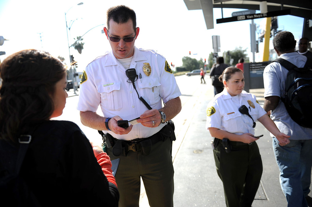 . LA County Sheriff security assistants check bus riders TAP cards during an Orange Line fare enforcement operation at the Van Nuys Orange Line Station February 25, 2014.  Officials from Metro and the Los Angeles Sheriff\'s Department Transit Services Bureau announced a new two-pronged effort to cut down on fare-evaders on the Orange Line by improving communications and beefing up enforcement.(Andy Holzman/Los Angeles Daily News)