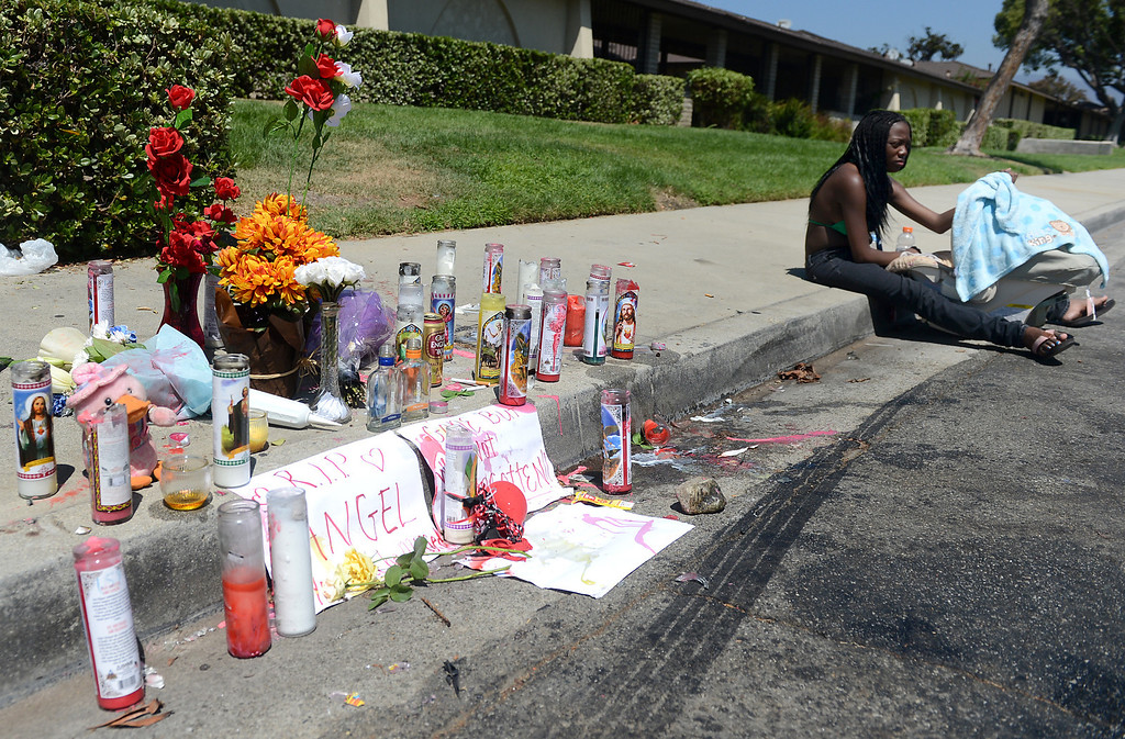 . Mia Hassan, 20, sits near the memorial for her boyfriend Angel Bravo with their five-week-old son, Remiel Bravo, Monday, August 12, 2013, in the 1700 block of Benedict Way in Pomona. Bravo, 29, was shot and killed while standing near his vehicle on a weekend morning.  (Staff photo/Inland Valley Daily Bulletin)