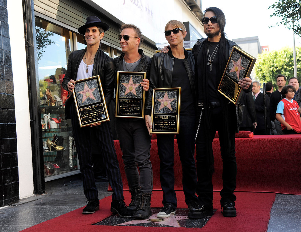 . Perry Farrell, from left, Stephen Perkins, Chris Chaney and Dave Navarro of the rock band Jane\'s Addiction pose in front of their new star on the Hollywood Walk of Fame, Wednesday, Oct. 30, 2013 in Los Angeles. (Photo by Chris Pizzello/Invision/AP)
