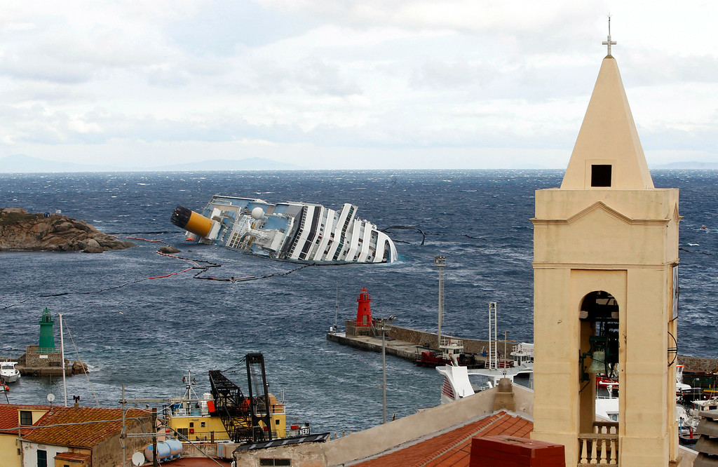 . The grounded cruise ship Costa Concordia lies on its side off the Tuscan island of Giglio, Italy, Wednesday, Feb. 1, 2012. Bad weather conditions forced the temporary suspension of the recovery operation of the capsized cruise ship Costa Concordia.The ship contains about 500,000 gallons (2,400 tons) of heavy fuel and other pollutants, and fears are growing that those pollutants could spill out, damaging a pristine environment that is home to dolphins, whales and other marine life. (AP Photo/Pier Paolo Cito)