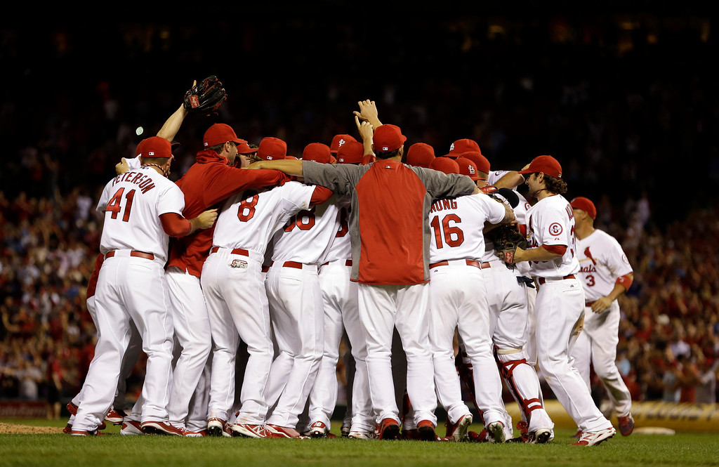 . Members of the St. Louis Cardinals celebrate after the Cardinals\' 7-0 win over the Chicago Cubs in a baseball game to clinch the NL Central title Friday, Sept. 27, 2013, in St. Louis. (AP Photo/Jeff Roberson)