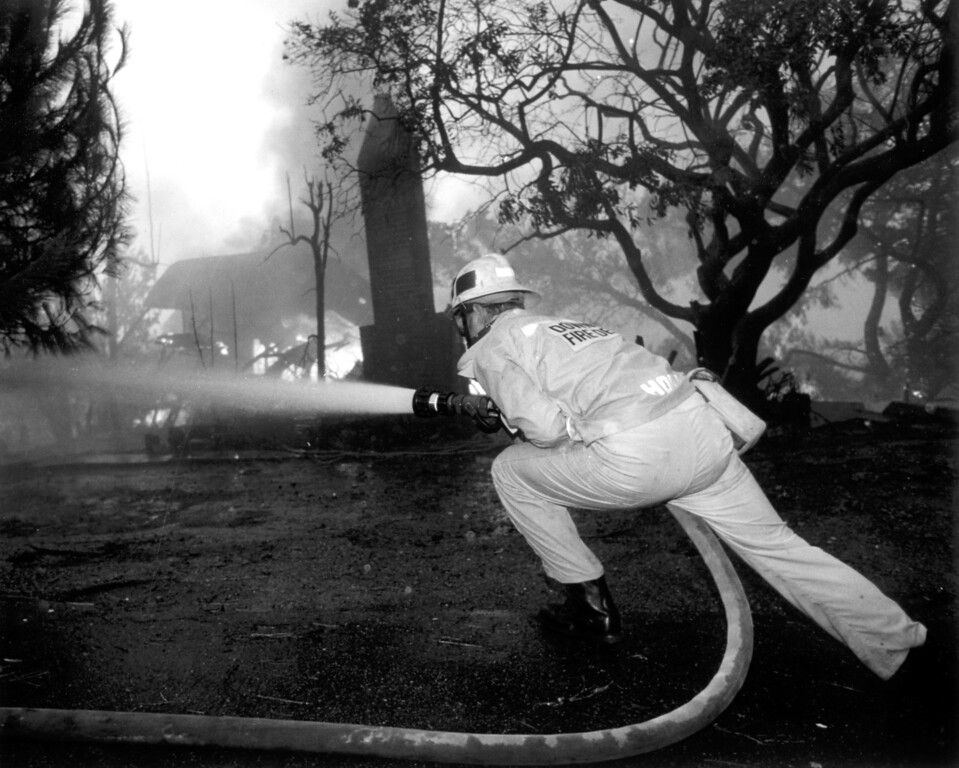 . A firefighter tries to control flames consuming a home on Rambla Pacifico in a hillside area above Malibu.  (11/2/93)   Los Angeles Daily News file photo