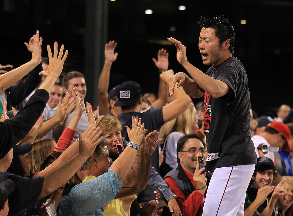 . BOSTON, MA - SEPTEMBER 20: Koji Uehara #19 of the Boston Red Sox celebrates with fans after winning the AL East Championship by beating  the Toronto Blue Jays at Fenway Park on September 20, 2013 in Boston, Massachusetts.  (Photo by Jim Rogash/Getty Images)