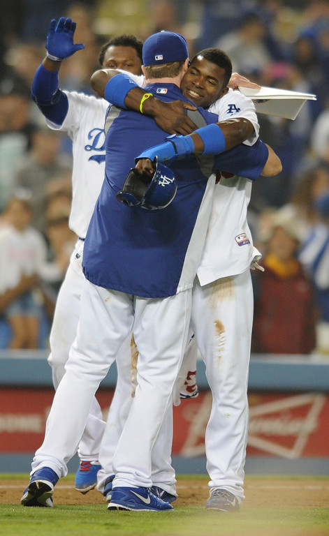 . Yasiel Puig gets a hug after the game as the Dodgers celebrate another win at home. The Dodgers defeated the New York Mets 5-4 in 12 innings at Dodger Stadium in Los Angeles, CA. 8/13/2013(John McCoy/LA Daily News)