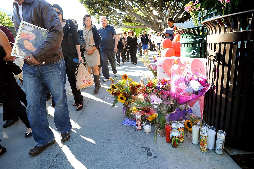 . Participants of a Monday night vigil make there way by a memorial at Santa Monica College June 10, 2013.(Andy Holzman/Los Angeles Daily News)