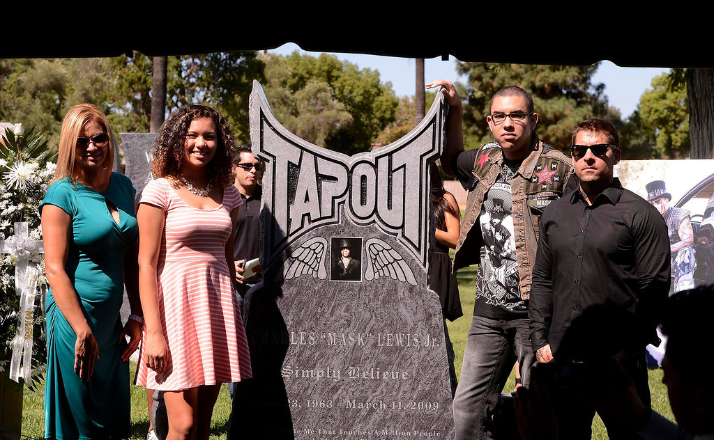 """. From left to right: Charles \""""Mask\"""" Lewis Jr.\'s family Diane Larson, Cheyenne Lewis, 18, and Boaz Lews, 20, stand with Tapout co-founder and president Dan Caldwell stand next to the newly unveiled monument for Charles Lewis Jr. at Mountain View Cemetery in San Bernardino, CA on Saturday September 7, 2013.   (Photo by Gabriel Luis Acosta/San Bernardino Sun)"""
