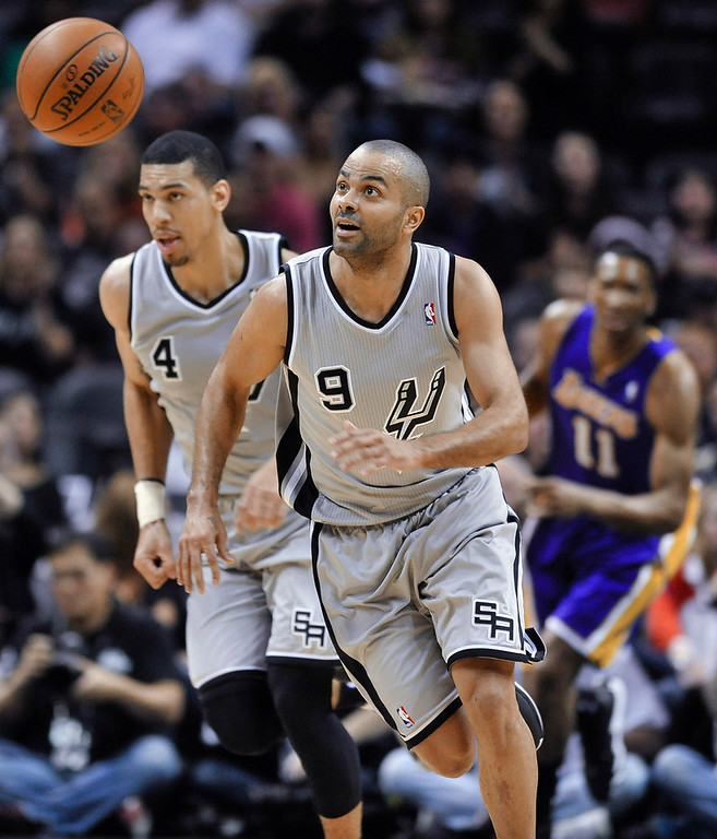 . San Antonio Spurs guard Tony Parker chases down a loose ball against the Los Angeles Lakers as teammate Danny Green follows in the first half of an NBA basketball game Friday, March 14, 2014, in San Antonio. The Spurs won 119-85. (AP Photo/Bahram Mark Sobhani)