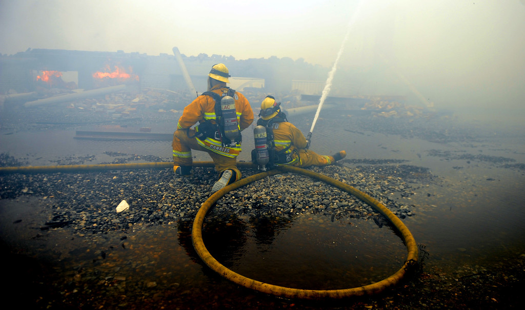 . Los Angeles County firefighters battle a 3-alarm fire in heavy smoke at an abandoned warehouse near 9th Avenue and Clark Avenue on Tuesday, July 9, 2013 in City of Industry, Calif.  (Keith Birmingham/Pasadena Star-News)