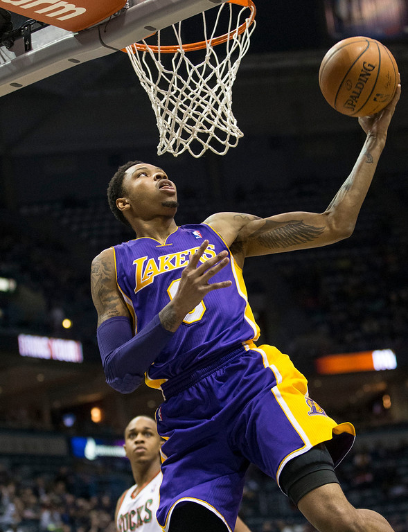 . Los Angeles Lakers\' Kent Bazemore drives past the Milwaukee Bucks  defense, but was called for a travel, during the first half of an NBA basketball game Thursday, March 27, 2014, in Milwaukee. (AP Photo/Tom Lynn)