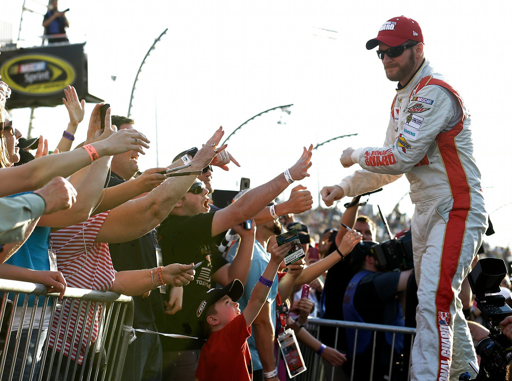 . Dale Earnhardt Jr., fist-bumps fans during driver introductions for the NASCAR Sprint Cup auto race at Richmond International Raceway in Richmond, Va., Saturday, April 26, 2014. (AP Photo/Steve Helber)