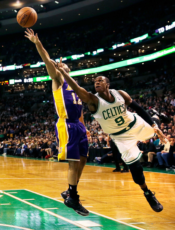 . Boston Celtics guard Rajon Rondo (9) follows through on a shot after driving past Los Angeles Lakers guard Kendall Marshall, left, during the second quarter of an NBA basketball game in Boston, Friday, Jan. 17, 2014. Rondo returned to the court for the first time this season, after undergoing surgery on his right knee. (AP Photo/Charles Krupa)