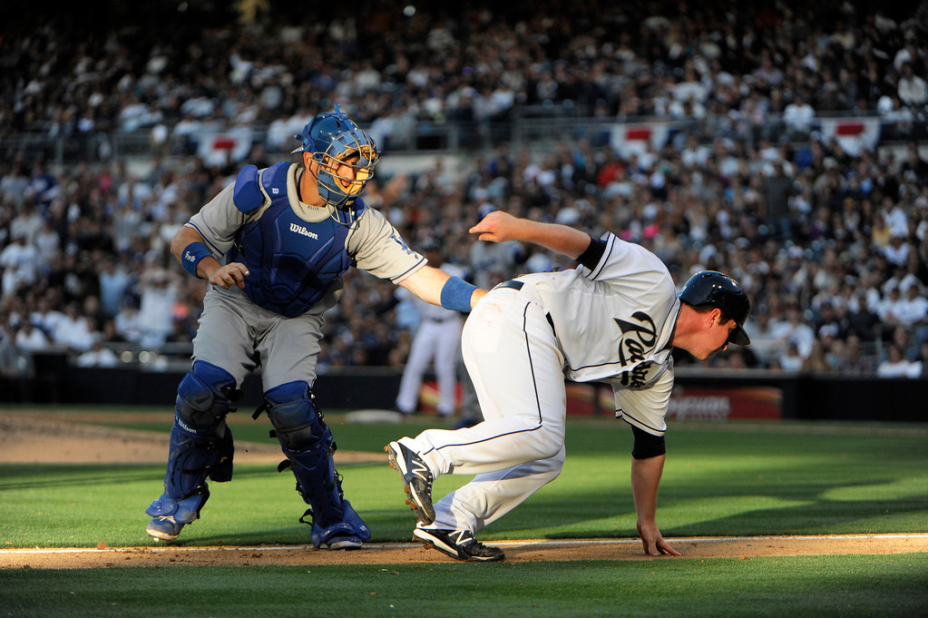 . Jedd Gyorko #9 of the San Diego Padres is tagged out by A.J. Ellis #17 of the Los Angeles Dodgers in a run down during the eighth inning of a baseball game at Petco Park on April 9, 2013 in San Diego, California. Padres won 9-3 (Photo by Denis Poroy/Getty Images)