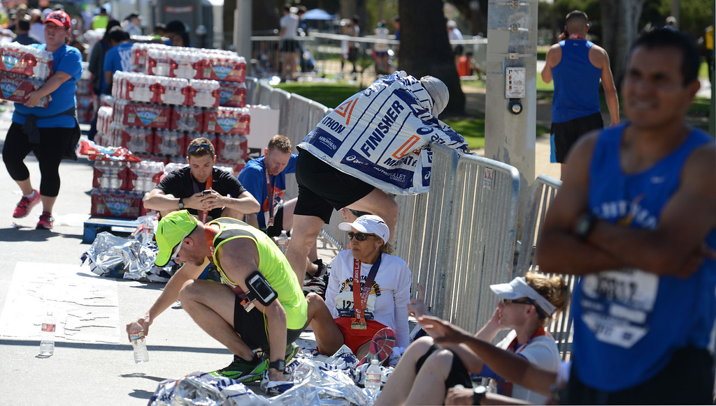 . Runners along Ocean Boulevard, after they  cross the finish line of  2014 ASICS LA Marathon finisher Bill Hopkins after feeling nauseous after he crossed the finish line in Santa Monica Calif,    Sunday, March 9,  2014. 