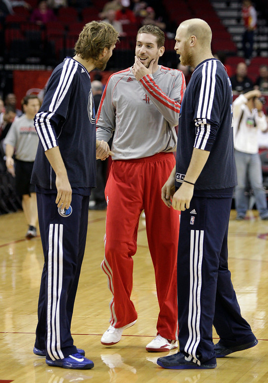 . Houston Rockets center Tim Ohlbrecht (14), of Germany, shakes hands during warm ups with Dallas Mavericks power forward Dirk Nowitzki (41), of Germany and Dallas Mavericks center Chris Kaman (35) during an NBA basketball game, Sunday, March 3, 2013 in Houston. Houston won 136-103. (AP Photo/Bob Levey)
