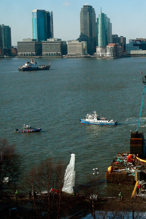 """. NEW YORK - JANUARY 16:  The wreckage of a wing of US Airways jetliner flight 1549 floats in the Hudson River as investigations begin on the accident on January 16, 2009 near Battery Park City in New York City. Yesterday the pilot, Chesley \""""Sully\"""" Sullenberger, 57, of the damaged plane landed the aircraft in the river with all 155 people aboard surviving.  (Photo by Mario Tama/Getty Images)"""
