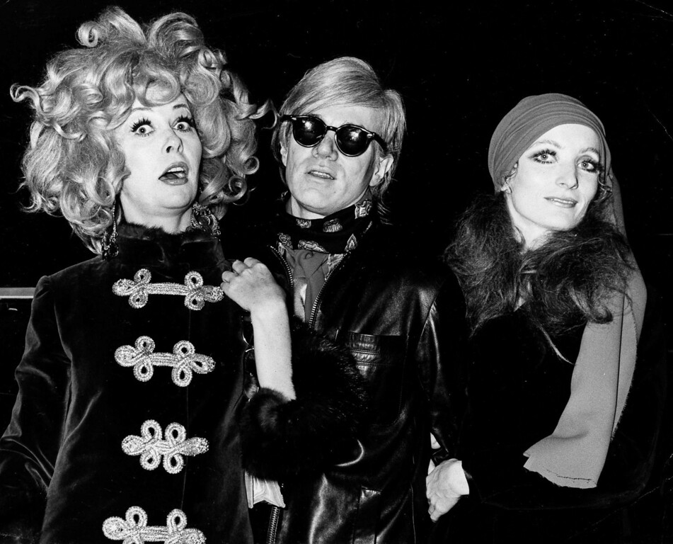 ". Pop artist Andy Warhol, center, accompanied by Factory regulars Ultra Violet, left and Viva, right, attend a preview of the film ""I Love You, Alice B. Toklas,\"" starring Peter Sellers and Leigh Taylor-Young, Oct. 1968. (AP Photo)"