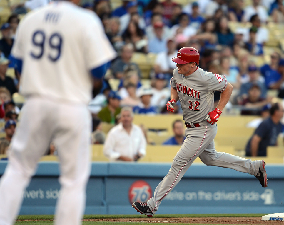 . The Dodgers\' Hyun-Jin Ryu #99 watches as the Reds\' Jay Bruce #32 heads for home after hitting a home run in the 2nd inning during their game at Dodger Stadium in Los Angeles Saturday, July 27, 2013. (Hans Gutknecht/Los Angeles Daily News)