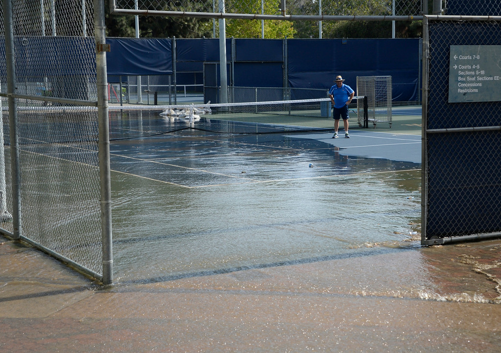 . July 29,2014. Westwood CA, Water makes its way onto the tennis courts after water main break sent a geyser of water blasting through Sunset Boulevard north of the UCLA campus Tuesday, sending mud and water cascading down the street and inundating a number of vehicles as it made its way onto the campus. Photo by Gene Blevins/LA DailyNews