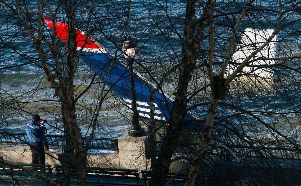 """. NEW YORK - JANUARY 16:  The tail of the wreckage of US Airways jetliner flight 1549 floats in the Hudson River as investigators hope to pull the craft from the river later today on January 16, 2009 near Battery Park City in New York City. Yesterday the pilot, Chesley \""""Sully\"""" Sullenberger, 57, of the damaged plane landed the aircraft in the river with all 155 people aboard surviving.  (Photo by Mario Tama/Getty Images)"""