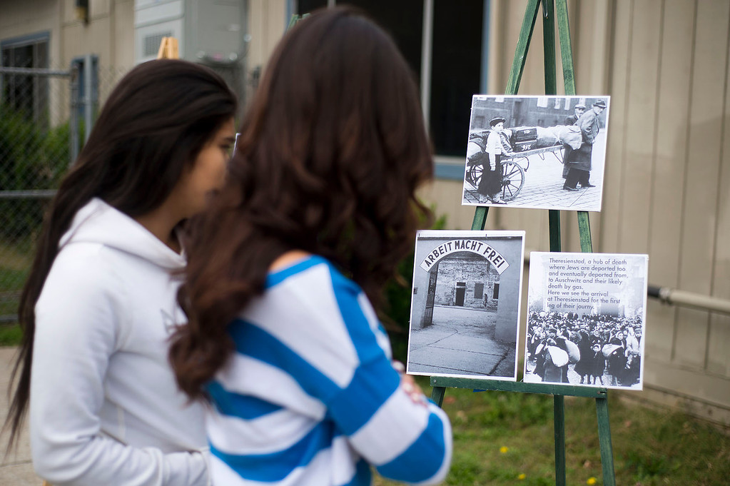 . Students look over photographs from the Holocaust at Sierra High School in Glendora on Tuesday, Nov. 12, 2013. (Photo by Watchara Phomicinda/San Gabriel Valley Tribune)