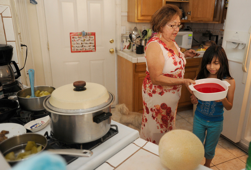 . Getting ready for dinner, Juanita Chavez, 69, of Los Angeles has raised her great-grandaughter Victoria Licea,7,since she was 1-month old. Chavez, who still has a home mortgage, works part-time giving manicures and pedicures at clients\' homes and struggles to make ends meet. Chavez is also taking care of her own daughter, who recently had a heart attack. A recent report by the UCLA Center for Health Policy Research has found that about 40 percent of older grandparents who are responsible for their grandchildren in the state do not have enough income to make ends meet.Los Angeles, CA. 7/11/2013(John McCoy/LA Daily News)