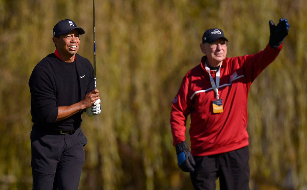 . Tiger Woods and a course marshall watch his tee shot on the fourth hole during the final round of the Northwestern Mutual World Challenge golf tournament at Sherwood Country Club, Sunday December 8, 2013, in Thousand Oaks, Calif.(Andy Holzman/Los Angeles Daily News)