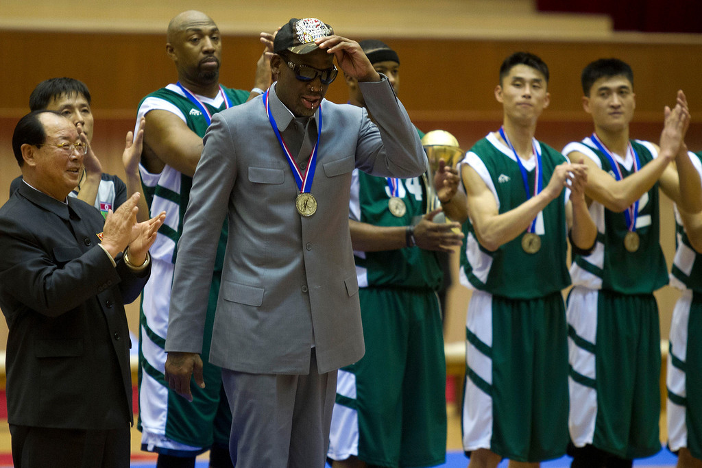 . Dennis Rodman tips his hat as U.S. and North Korean basketball players applaud at the end of an exhibition basketball game at an indoor stadium in Pyongyang, North Korea on Wednesday, Jan. 8, 2014. Behind him at right is former NBA player Vin Baker. (AP Photo/Kim Kwang Hyon)