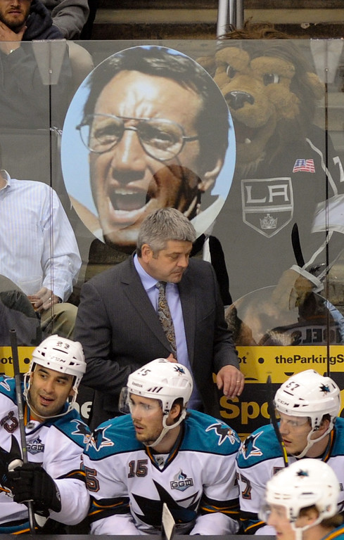 """. Kings\' mascot Bailey holds a picture of actor Roy Scheider from the movie \""""Jaws\"""" behind Sharks\' head coach Todd McLellan. (Michael Owen Baker/Staff Photographer)"""