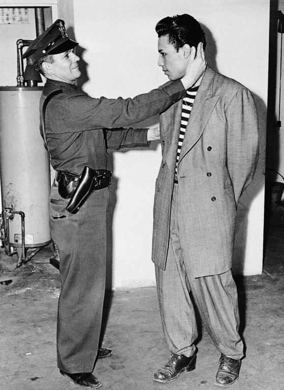 """. Deputy Sheriff Bartley Brown of East Los Angeles inspects the haircut of prisoner Alex \""""Largo\"""" Rodriguez, who is wearing an $85.00 zoot suit June 7, 1943. (AP Photo)"""