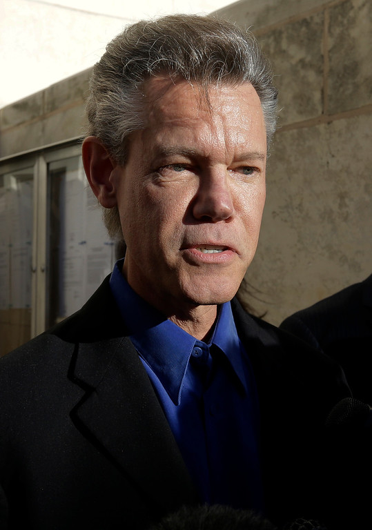 . FILE - In this Jan. 31, 2013 file photo, country star Randy Travis makes comments after exiting the Grayson County Courthouse, in Sherman, Texas. Travis has filed a lawsuit to prevent two state agencies from releasing a patrol car video of his 2012 DWI arrest in North Texas. (AP Photo/Tony Gutierrez, File)