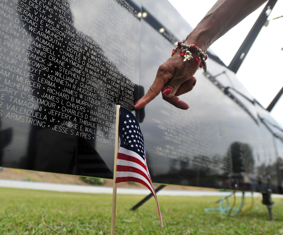 ". A resident touches the name of a high school classmate at the ""Wall that Heals\"" traveling replica of the Vietnam Veterans Memorial wall at La Habra High School in La Habra on Thursday July 11, 2013. The wall will be in the stadium until the closing ceremony on Sunday. (SGVN/Staff Photo by Keith Durflinger)"