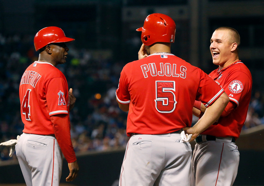 . Los Angeles Angels first base coach Alfredo Griffin (4) and Albert Pujols (5) laugh with Mike Trout during a pitching change for the Chicago Cubs in the fifth inning of an interleague baseball game Wednesday, July 10, 2013, in Chicago. (AP Photo/Charles Rex Arbogast)