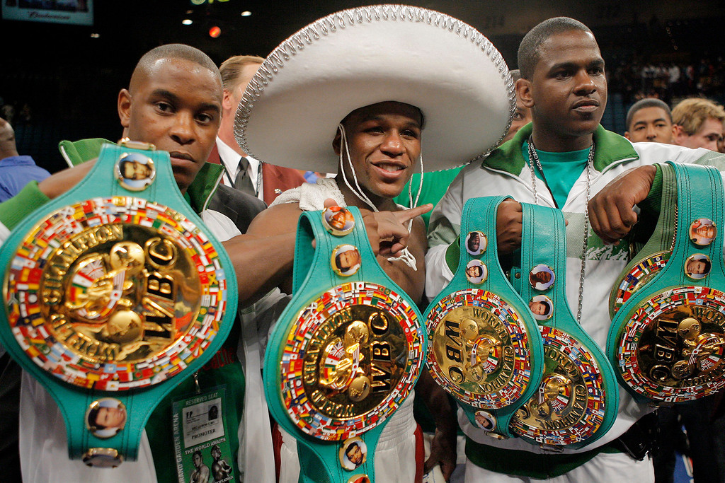 . Floyd Mayweather Jr., center,  poses with his title belts after defeating Oscar De La Hoya in a split decision following their WBC super welterweight world championship boxing match on Saturday, May 5, 2007, at the MGM Grand Garden Arena  in Las Vegas.  (AP Photo/Jae C. Hong)