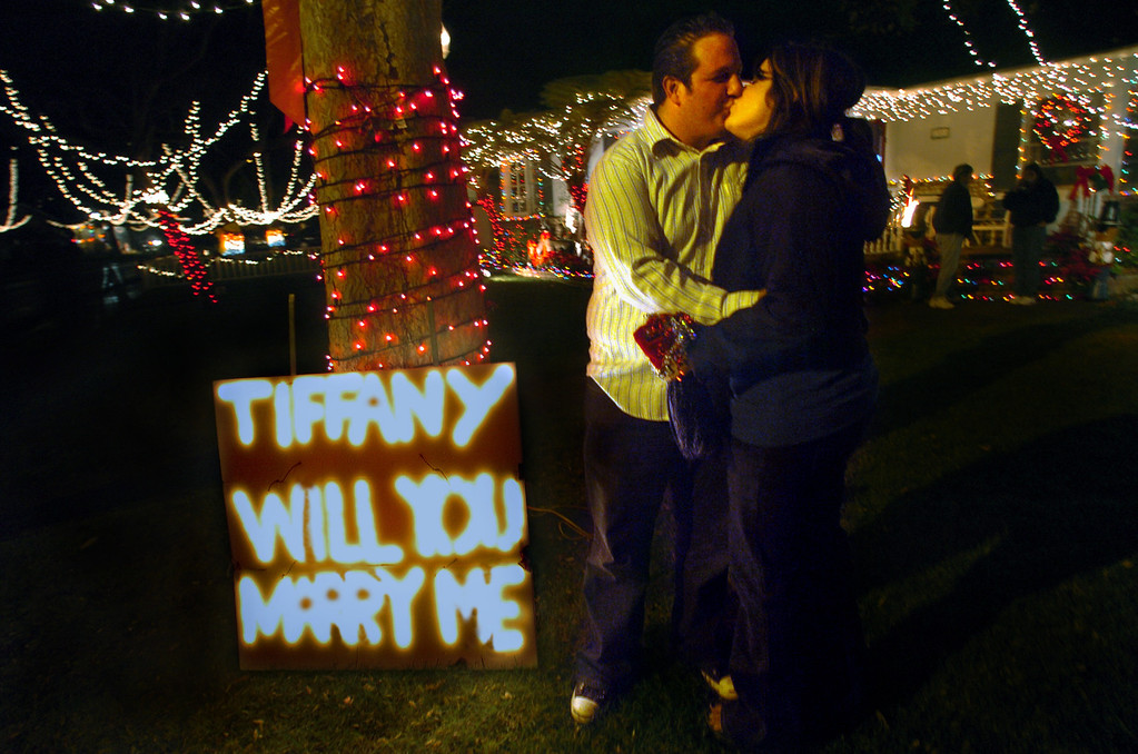 . San Pedro residents Christopher Ciolino and Tiffany Fellows embrace after she accepted his marriage proposal at Sleepy Hollow Saturday night. Ciolino, who had the sign put up at the corner of Reese Road and Doris Way, drove to Sleepy Hollow during their annual visit to pop her the marriage question... Fellows accepted. Photo/Bruce Hazelton 12/16/06
