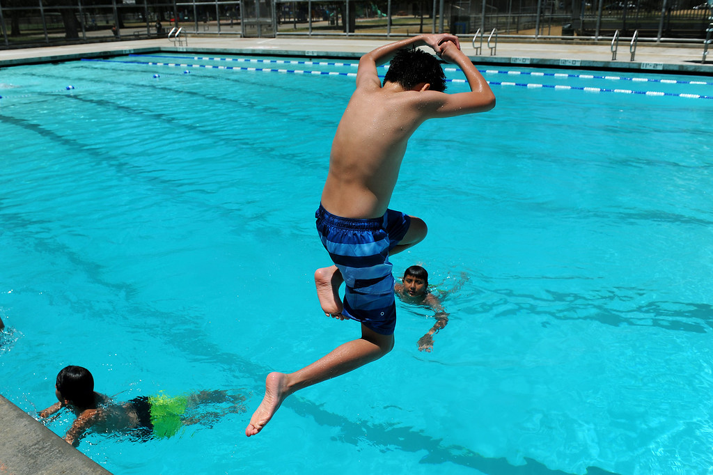 ". Matthew Susanto, 13, does the ""margarita\"" dive at the Lanark Park pool in Canoga Park, Saturday, June 14, 2014. (Photo by Michael Owen Baker/Los Angeles Daily News)"