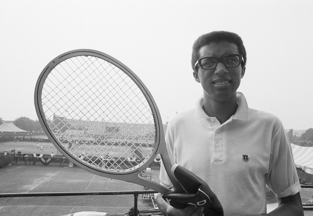 """. Tennis star Arthur Ashe, the number 1 U.S. Davis Cup player from Richmond, Va., poses with his new racket, Aug. 31, 1969, at Forest Hills, N.Y., where he is competing in the $137,000 U.S. Open tennis championship. The racket is gray in color and his made of layers of glass, aluminum and wood. \""""It\'s what they call a sandwich,\"""" said Ashe.  (AP Photo/Harry Harris)"""