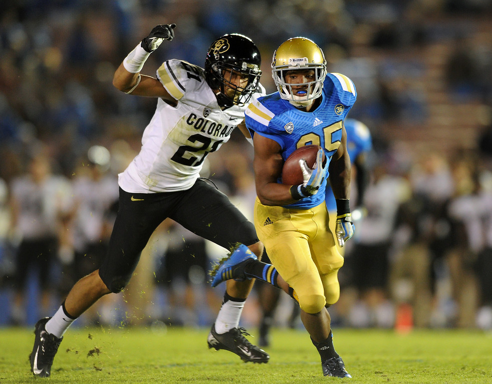 . UCLA RB Damien Thigpen runs for a 27-yard gain before being brought down by Colorado\'s Jered Bell in the fourth quarter, Saturday, November 2, 2013, at the Rose Bowl. (Photo by Michael Owen Baker/L.A. Daily News)