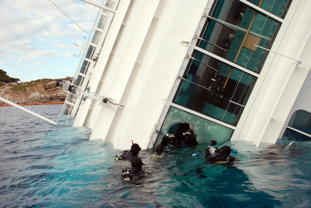 . In this undated photo released by Carabinieri (Italian paramilitary police) Friday, Jan. 20, 2012 Carabinieri scuba divers swim close to the Costa Concordia cruise ship, off the tiny Giglio island, Italy. The $450 million Costa Concordia was carrying more than 4,200 passengers and crew when it slammed into well-marked rocks off the island of Giglio after the captain made an unauthorized diversion from his programmed route. The ship then keeled over on its side. (AP Photo/Carabinieri)