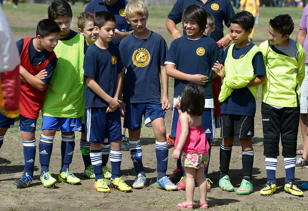 . Youth soccer players listen to a little sister who may have been commenting on the poor condition of the grass field they are standing on. Councilmember Tom LaBonge joined the Los Angeles Department of Recreation and Parks, LA Bureau of Engineering and a group of young soccer players to break ground on three new synthetic turf soccer fields at the Van Nuys Sherman Oaks Park. The $2.7-million renovation will include synthetic fields that can be used year round. Also planned are new paved walkways and benches. Sherman Oaks, CA. 7/1022014(Photo by John McCoy Daily News)