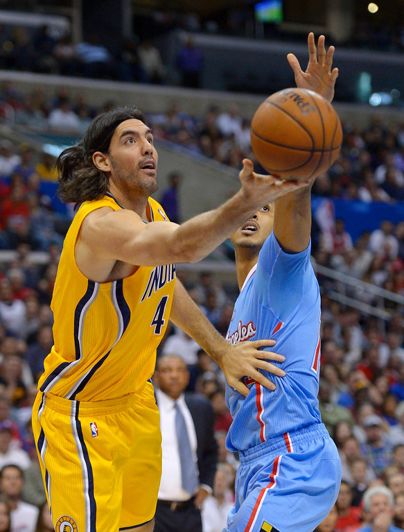 . Indiana Pacers forward Luis Scola, left, of Argentina, puts up a shot as Los Angeles Clippers center Ryan Hollins defends during the first half of an NBA basketball game, Sunday, Dec. 1, 2013, in Los Angeles. (AP Photo/Mark J. Terrill)
